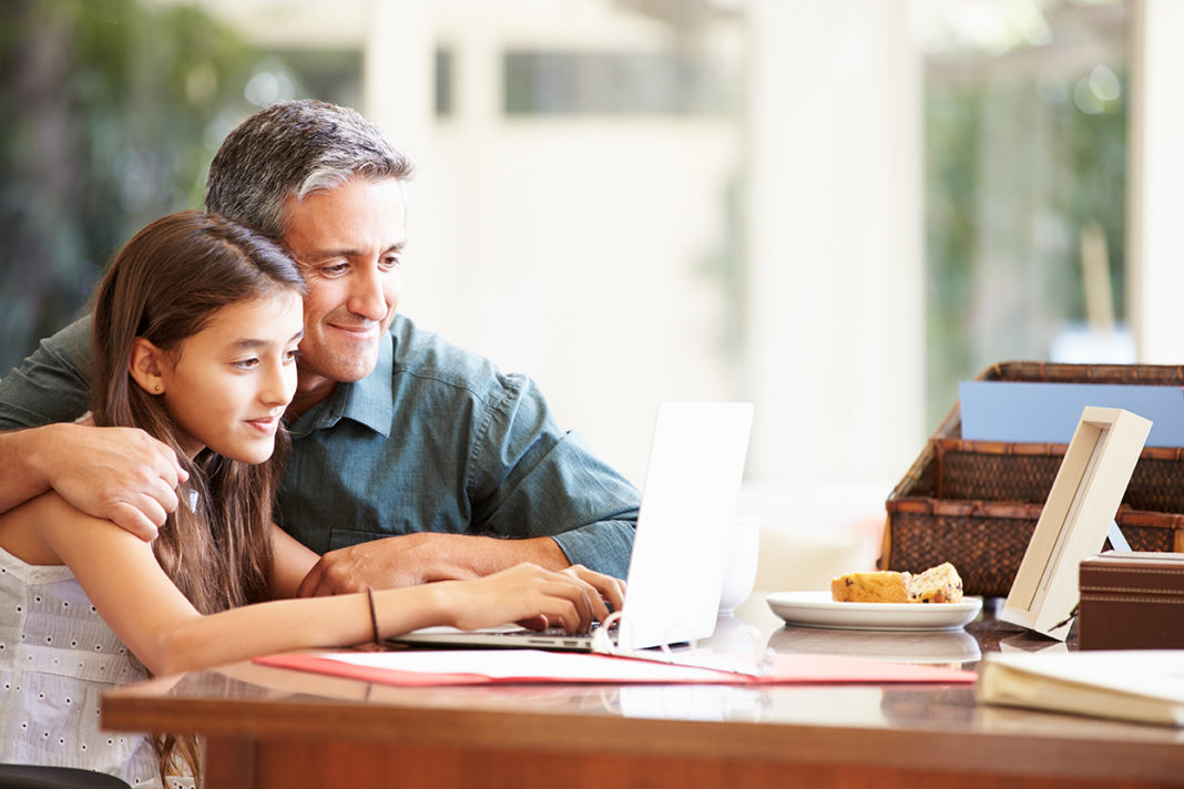 Father And Teenage Daughter Looking At Laptop Together